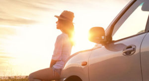 Woman sitting on hood of car during sunset