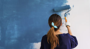 Woman painting white wall blue with roller
