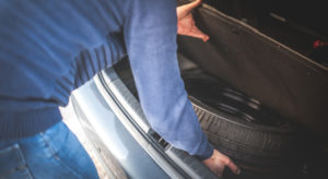 man getting spare tire from car trunk