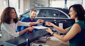 Couple buying a car at new car dealership