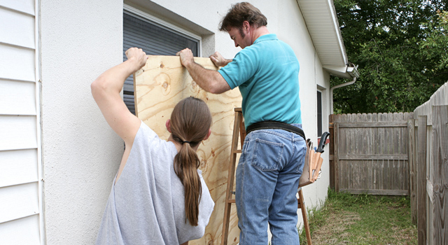 two men placing plywood over a window preparing for a hurricane
